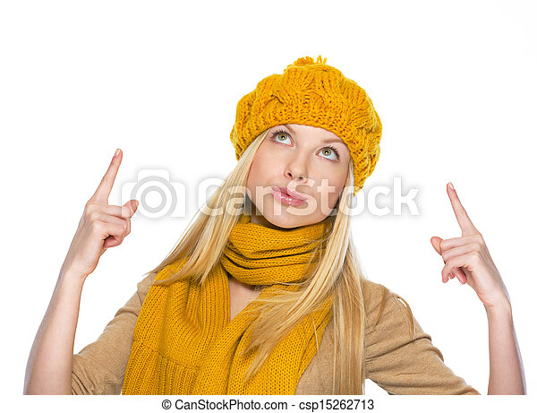 Young woman in hat and scarf pointing up on copy space - csp15262713