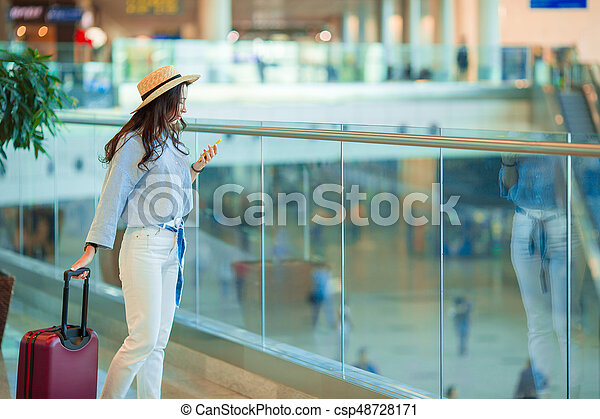 Young woman in hat with baggage in international airport walking with her luggage. Airline passenger in an airport lounge waiting for flight aircraft - csp48728171