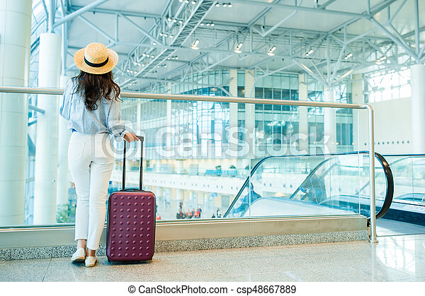 Young woman in hat with baggage in international airport walking with her luggage. Airline passenger in an airport lounge waiting for flight aircraft - csp48667889