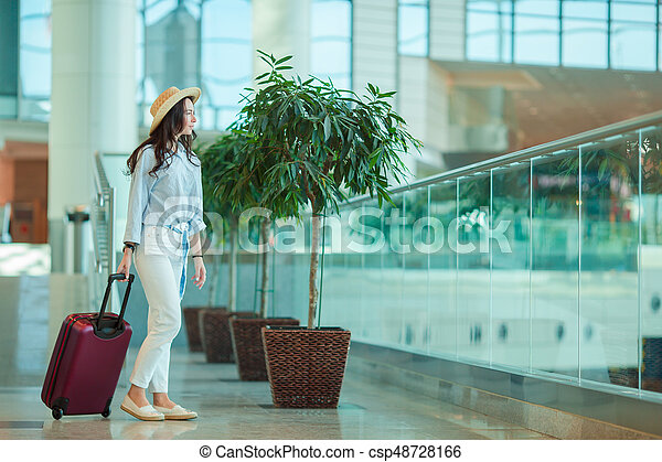 Young woman in hat with luggage in international airport. Airline passenger in an airport lounge waiting for flight aircraft - csp48728166