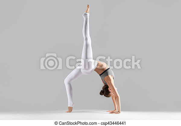 122c72cc2984c Young woman in one legged wheel pose, grey studio background. Young ...