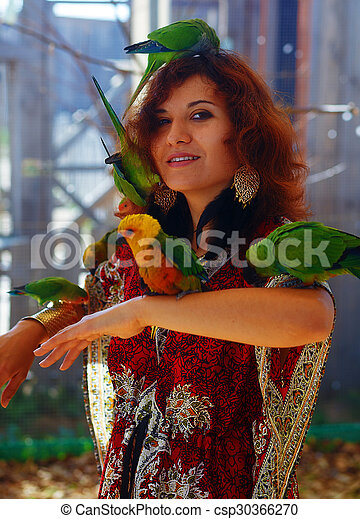 Young woman in ornamental dress and beautiful gold jewelry with a color parrots - csp30366270