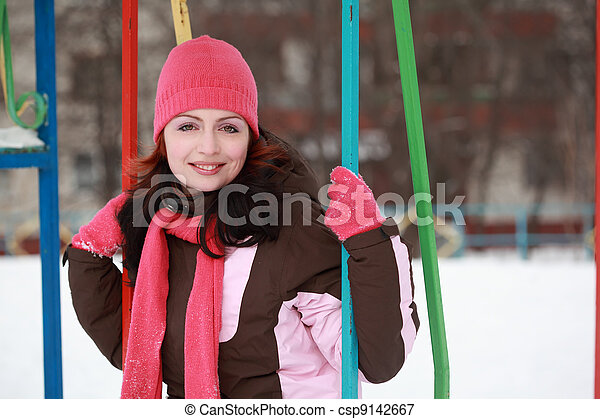 young woman in pink hat sitting on swing in winter, children's playground - csp9142667