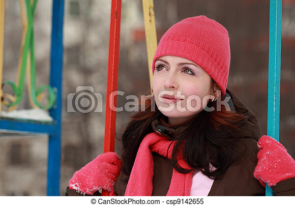 young woman in pink hat sitting on swing in winter, children's playground - csp9142655