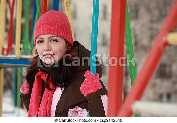 young woman in pink hat sitting on swing and smiling in winter, children's playground - csp9142640