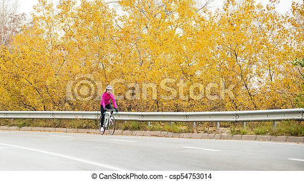 Young Woman in Pink Jacket Riding Road Bicycle on the Highway in the Cold Autumn Day. Healthy Lifestyle. - csp54753014