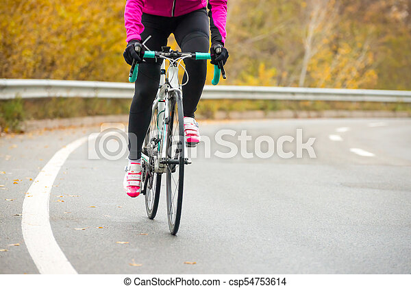 Young Woman in Pink Jacket Riding Road Bicycle on the Highway in the Cold Autumn Day. Healthy Lifestyle. - csp54753614