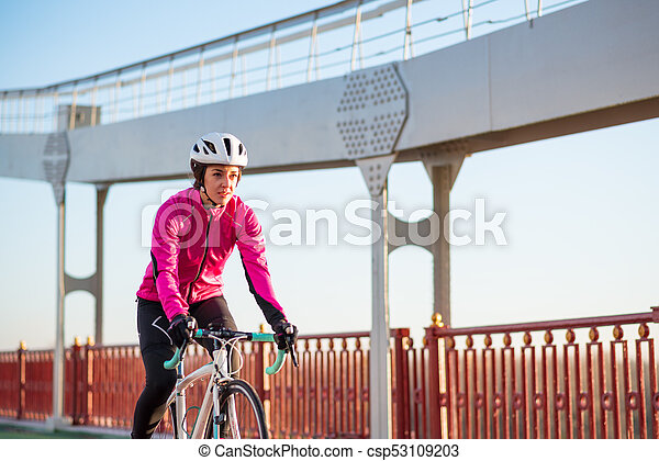 Young Woman in Pink Jacket Riding Road Bicycle on the Bridge Bike Line in the Cold Sunny Autumn Day. Healthy Lifestyle. - csp53109203