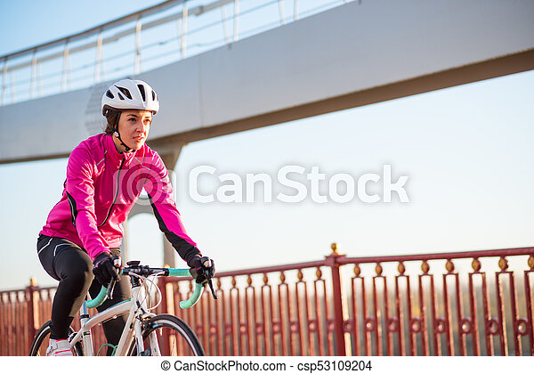 Young Woman in Pink Jacket Riding Road Bicycle on the Bridge Bike Line in the Cold Sunny Autumn Day. Healthy Lifestyle. - csp53109204