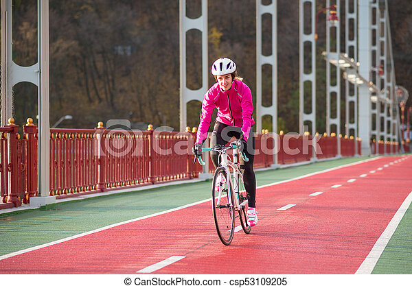 Young Woman in Pink Jacket Riding Road Bicycle on the Bridge Bike Line in the Cold Sunny Autumn Day. Healthy Lifestyle. - csp53109205