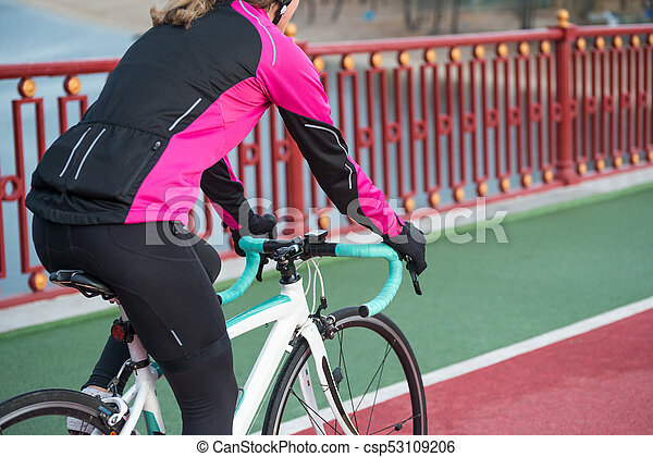 Young Woman in Pink Jacket Riding Road Bicycle on the Bridge Bike Line in the Cold Sunny Autumn Day. Healthy Lifestyle. - csp53109206