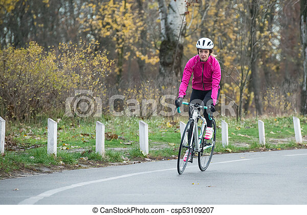 Young Woman in Pink Jacket Riding Road Bicycle in the Park in the Cold Autumn Day. Healthy Lifestyle. - csp53109207