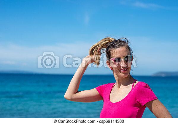 Young woman in pink shirt enjoying holidays at the seaside - csp69114380