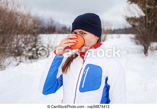 Young woman in winter sport jacket drinking hot tea from orange thermos flask cup on cold overcast day with snow covered landscape in background. - csp58874413