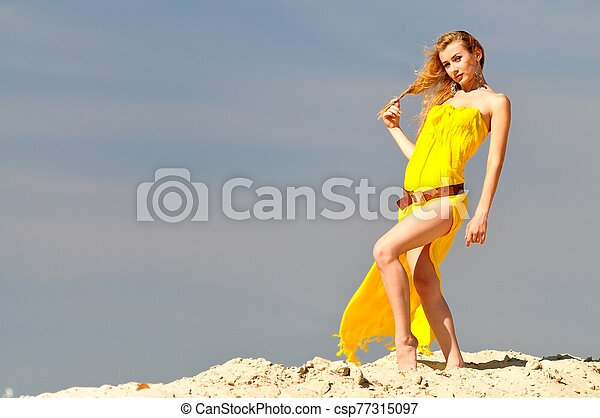 Young woman in yellow dress standing on sandy hill - csp77315097