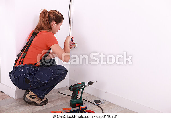 Young Woman Installing Electricity In A House   Csp8110731