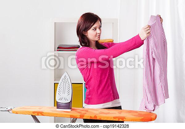 Young woman ironing shirt - csp19142328