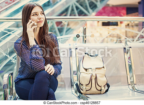 Young woman is sitting at an airport and speaking by her phone. - csp46128857