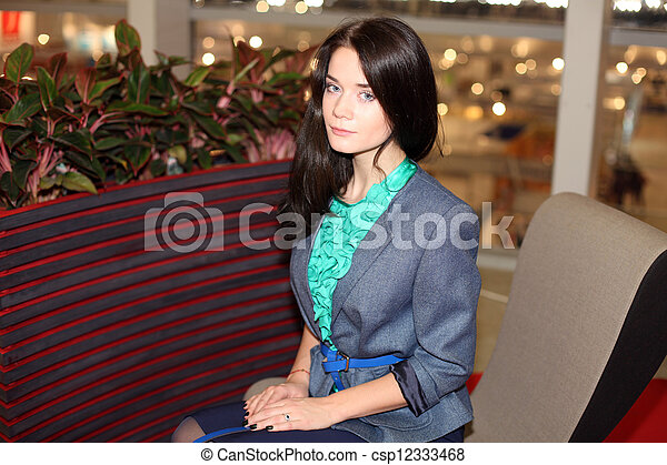 young woman is sitting in an chair - csp12333468