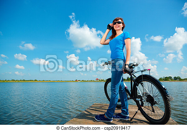 Young woman is standing in front of her bicycle - csp20919417