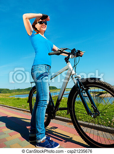 Young woman is standing in front of her bicycle - csp21235676