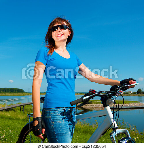 Young woman is standing in front of her bicycle - csp21235654