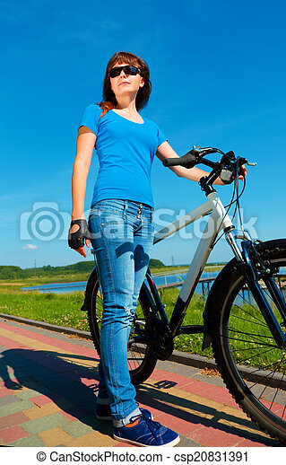 Young woman is standing in front of her bicycle - csp20831391