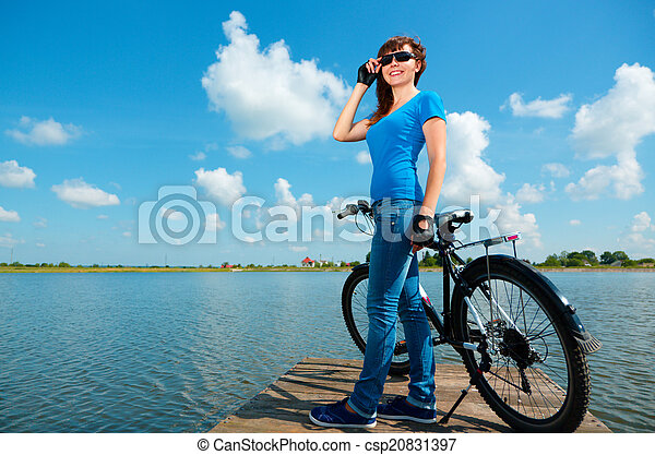 Young woman is standing in front of her bicycle - csp20831397