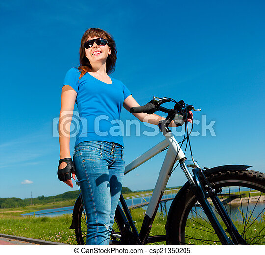 Young woman is standing in front of her bicycle - csp21350205