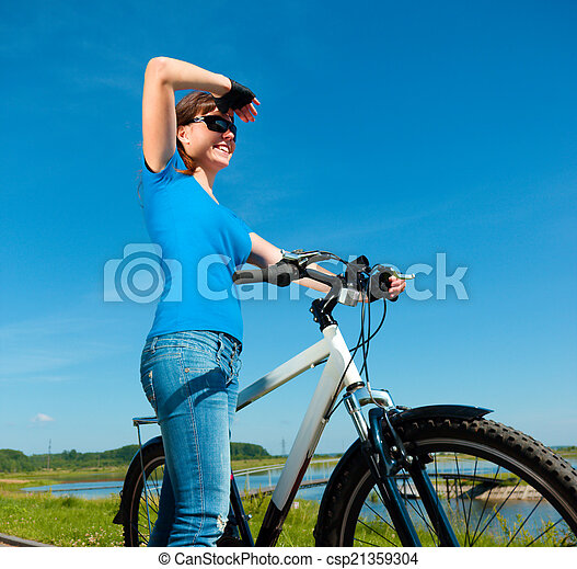 Young woman is standing in front of her bicycle - csp21359304