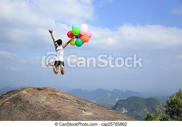 young woman jumping mountain peak - csp25765862