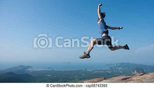 Young woman jumping on mountain peak cliff edge - csp58743393