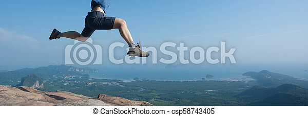Young woman jumping on mountain peak cliff edge - csp58743405