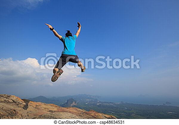 Young woman jumping on mountain peak - csp48634531