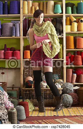 Young Woman Knitting Scarf Standing In Front Of Yarn Display - csp7428045