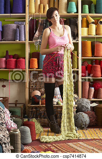 Young Woman Knitting Scarf Standing In Front Of Yarn Display - csp7414874