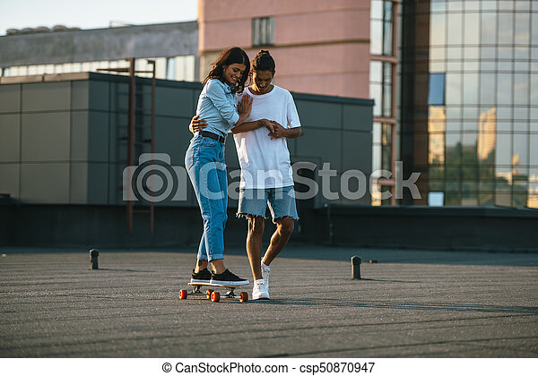 young woman learning to ride skateboard - csp50870947