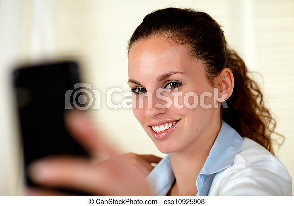 Young woman looking and smiling to cellphone - csp10925908