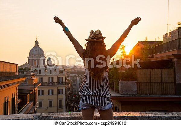 Young woman looking on rooftops of rome on sunset and rejoicing. - csp24994612