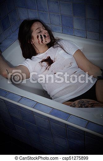 Young woman lying dead in bath tub.