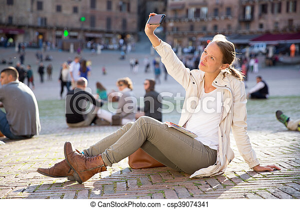 Young woman messaging/using app on her smart-phone in a city street context - csp39074341