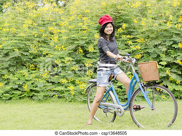 Young woman on a green meadow with a bicycle  - csp13648505