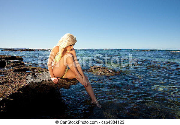 young woman on rock at beach - csp4384123