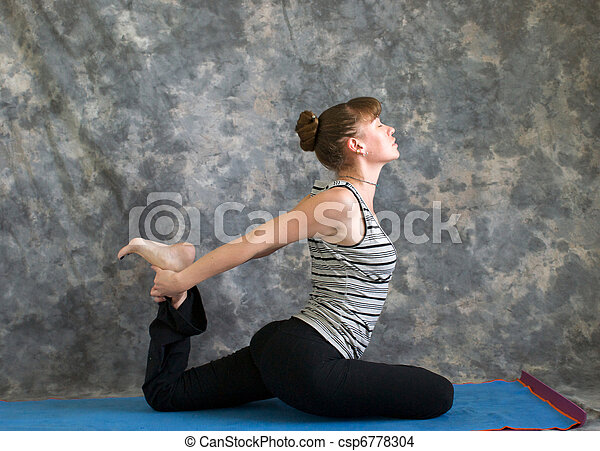 Young woman on yoga mat  doing Yoga posture Kapotasana or Pigeon Pose against a grey background in profile, facing right lit by diffused sunlight. - csp6778304