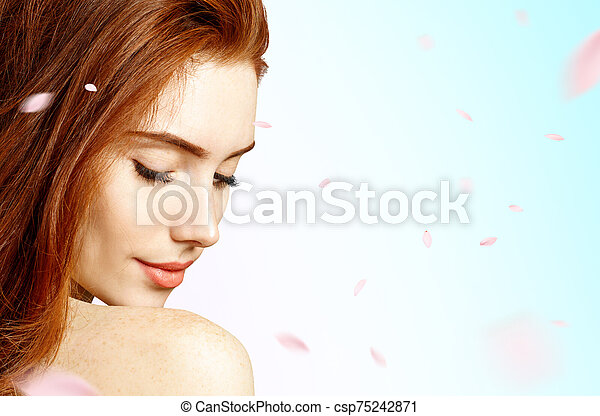 Young woman over fresh blue background with swirl petals. - csp75242871