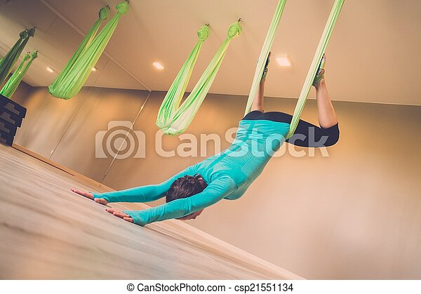 Young woman performing antigravity yoga exercise  - csp21551134