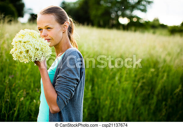 Young woman picking elderflower to make an infusion at home - csp21137674