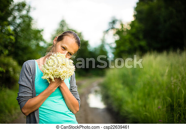 Young woman picking elderflower to make an infusion at home - csp22639461