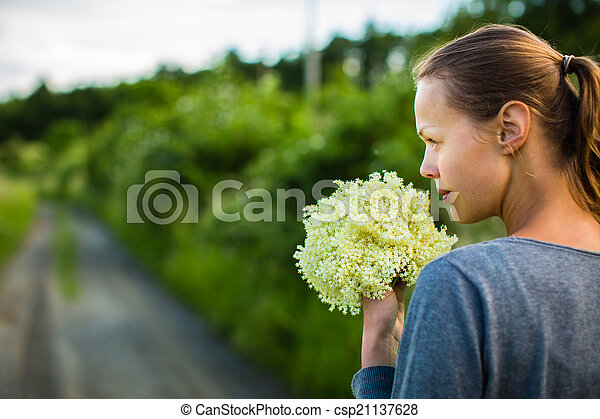 Young woman picking elderflower to make an infusion at home - csp21137628