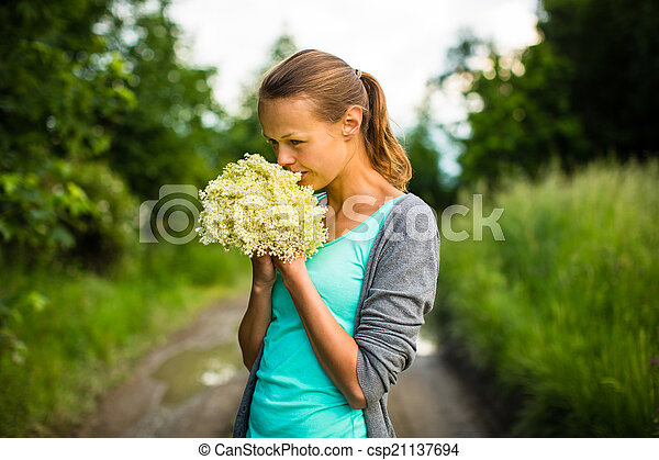 Young woman picking elderflower to make an infusion at home - csp21137694
